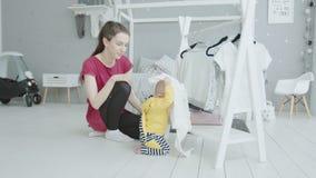 Baby die dingen bestuderen onder de supervisie van het mamma binnen stock video