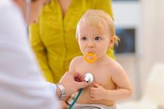 Baby die door arts wordt gecontroleerd die stethoscoop met behulp van stock fotografie