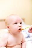 Baby die door plastic lepel eet Stock Afbeeldingen