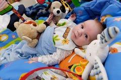 Baby die door speelgoed wordt omringd royalty-vrije stock afbeelding