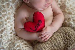 Baby die een Hart Gevormd Hoofdkussen houden Stock Afbeelding