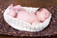 Baby die in een mand leggen stock afbeelding