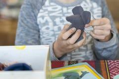 Baby die een zacht stuk speelgoed met katoen vullen ig Haak stuk speelgoed voor kind Voor lijstdraden, naalden, haak, katoenen ga royalty-vrije stock foto