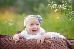 Baby die en omhoog aan camera in openlucht in zonlicht glimlachen kijken Stock Foto