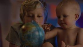Baby die enkel bij slecht zitten en met bol en zijn broer de spelen maakt bedrijf tot dichte omhooggaand stock video