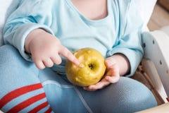Baby die fruit eten Weinig jongen het bijten appelzitting als witte hoge voorzitter in zonnige keuken met venster en gootsteen Ge royalty-vrije stock foto