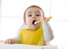 Baby die gezond voedsel met de linkerhand thuis eten stock foto's