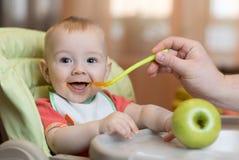 Baby die gezond voedsel met vaderhulp thuis eten royalty-vrije stock afbeelding