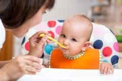 Baby die gezond voedsel op keuken eten stock foto