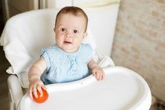 Baby die groenten eten de rode tomaat in meisje dient zonnige keuken in Gezonde voeding voor jonge geitjes Snack of ontbijt voor  royalty-vrije stock afbeeldingen