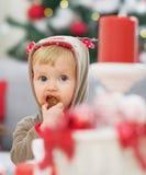 Baby die in Kerstmiskostuum koekje eten stock afbeeldingen