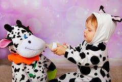 Baby die in koekostuum een koemascotte voedt stock foto's