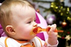 Baby die met een lepel bij Kerstmis eten Stock Afbeelding