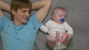 Baby die met vader rusten stock video
