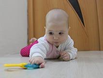 Baby die na een stuk speelgoed kruipen stock afbeelding