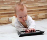 Baby die nota's over zijn tabletpc maakt Stock Foto's