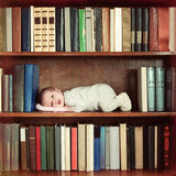 Baby die op boekenplank in boekenkast liggen royalty-vrije stock foto