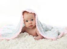 Baby die op buik onder deken ligt Stock Foto's