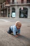 Baby die op de straat en het glimlachen kruipen stock afbeelding