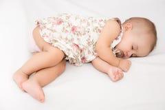 Baby die op een bed liggen terwijl het slapen in een heldere ruimte Royalty-vrije Stock Foto's