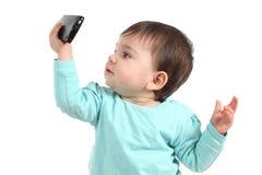 Baby die op een mobiele telefoon letten Stock Afbeeldingen