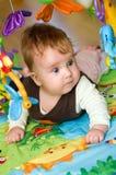 Baby die op Kleurrijke Mat legt royalty-vrije stock afbeelding
