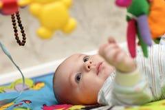 Baby die op mat ligt Stock Foto
