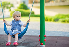 Baby die op schommeling op speelplaats slingert. Zijaanzicht Stock Afbeelding