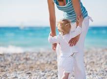 Baby die op strand moedershanden beklimt Royalty-vrije Stock Foto