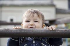 Baby die pret hebben terwijl het hangen op houten bar Stock Fotografie