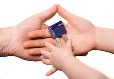 Baby die sleutels van de handen van ouders neemt Stock Foto's