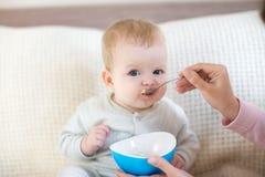 Baby die terwijl het situeren op het bed eten Royalty-vrije Stock Afbeeldingen