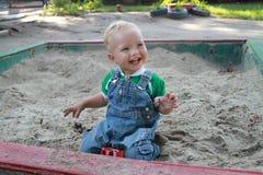 Baby die terwijl het spelen in de zandbak met zand lachen Stock Foto's