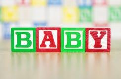 Baby die uit in de Bouwstenen van het Alfabet wordt gespeld Stock Foto's