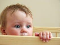 Baby die van zijn bed kijkt Stock Fotografie