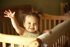 Baby die in voederbak opstaat Stock Afbeelding
