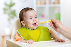 Baby die voedsel op keuken eten stock afbeelding