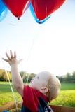 Baby die voor Ballons bereikt Stock Afbeelding