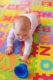 Baby die voor kop op alfabetmat bereiken Royalty-vrije Stock Foto's
