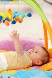 Baby die voor stuk speelgoed bereikt stock fotografie