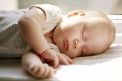 Baby die witte deken op venster slapen Stock Afbeeldingen