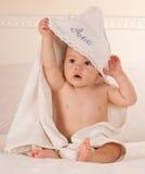 Baby die zijn handdoek opstijgt stock foto