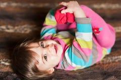 Baby die zijn voeten het glimlachen houden Stock Afbeelding