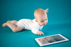 Baby with digital tablet. Baby girl on blue background Royalty Free Stock Image
