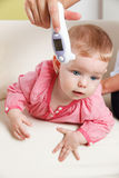 Baby with a digital thermometer Stock Image