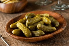 Baby Dill Pickles. A bowl of baby dill pickles on a rustic wood table top stock image