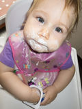 Baby dirty face white yogurt in high-chair Stock Images