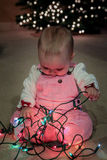 Baby discovering Christmas light string Royalty Free Stock Images