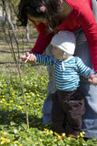 Baby discovering nature. Mother helping baby to make the first steps, springtime Stock Photo