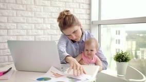 Baby distraherade modern från konversation Modern kvinna som hemifrån arbetar stock video